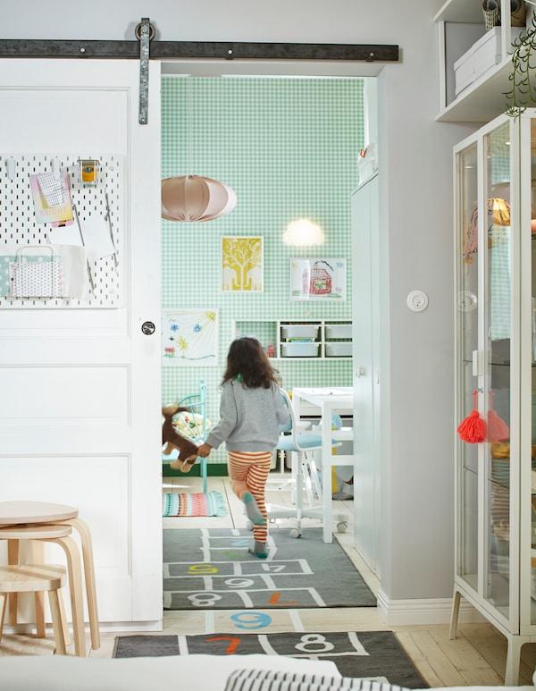 Ein Kind rennt durch eine offene Schiebetür eines in Weiß und Grün eingerichteten Zimmers mit Bett, Aufbewahrung, einem Schreibtisch und einem HEMMAHOS Teppich.