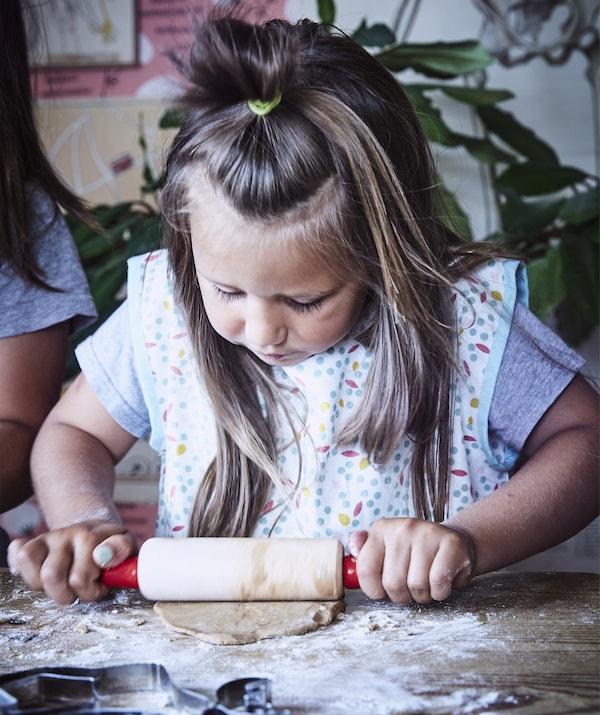 Ein Kind rollt auf einer Arbeitsfläche Teig aus und trägt dabei SPRUDLA Kinderschürze mit Punkten.