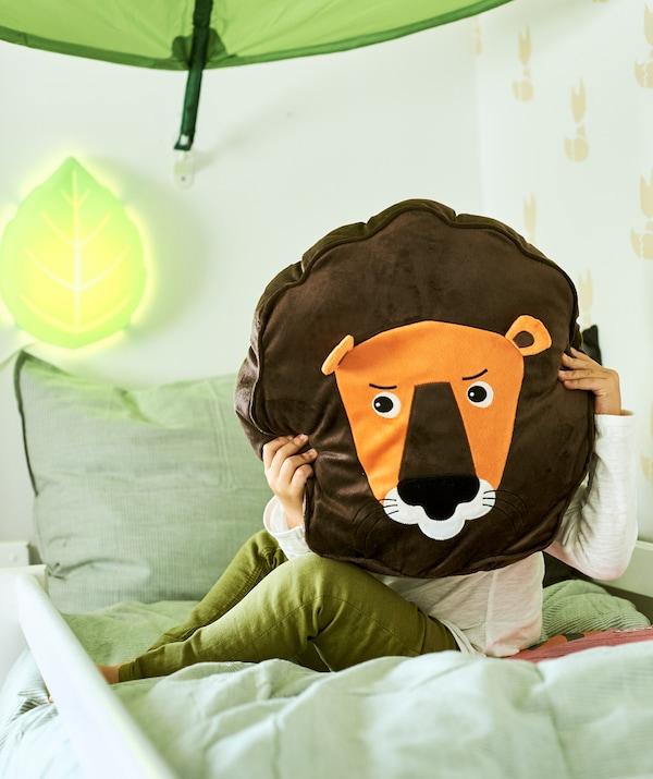 Ein Kind sitzt auf einem Bett und hält sich ein DJUNGELSKOG Kissen in Löwenform vors Gesicht.