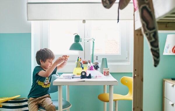 Ein Kind sitzt auf einem ÖRFJÄLL Schreibtischstuhl für Kinder an einem weissen Schreibtisch und malt etwas aus. Gegenüber steht ein gelber Stuhl.