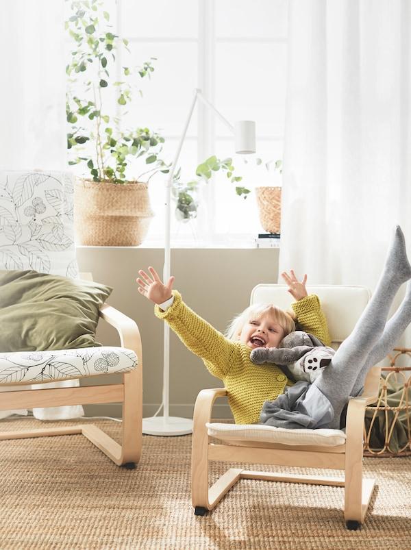 Ein Kind sitzt fröhlich mit einem Stofftier in einem POÄNG Kindersessel, der neben einem normalgrossen Exemplar steht.