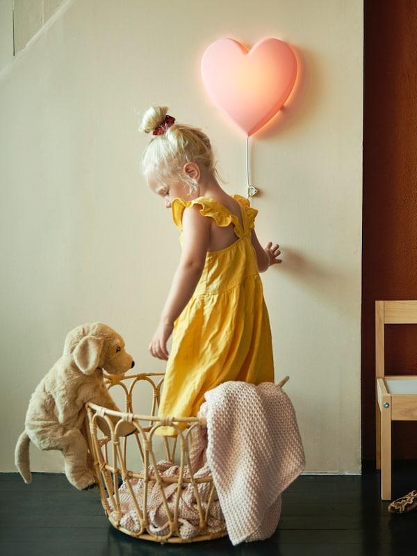 Ein Kind steht in einem Korb und schaltet eine Kinderleuchte in Herzform von IKEA die an der Wand hängt ein.