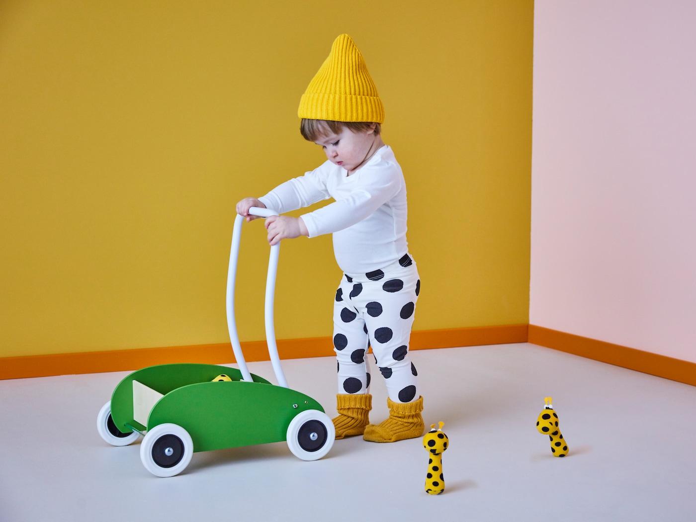 Ein Kind trägt einen gelben Hut und schwarz-weiß gepunktete Leggins. Es schiebt einen MULA Wagen zum Laufenlernen vor sich her.