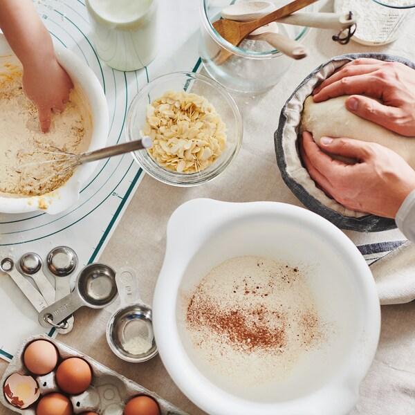 Ein Kind und ein Erwachsener stehen an einem Tisch und sind mit den VISPAD Rührschüsseln, Eiern, Mehl und Backutensilien in eine Backaktivität vertieft.