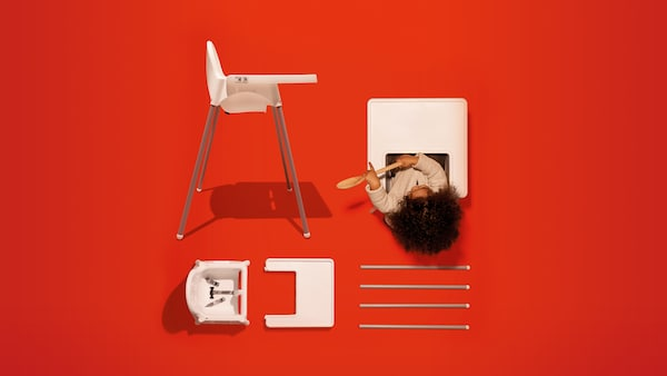 Ein Kinderhochstuhl mit einem Tablett in Weiss. Ein Kind sitzt darin und spielt mit einem Löffel. Daneben liegen die Teile eines weiteren Hochstuhls auf einem roten Untergrund.