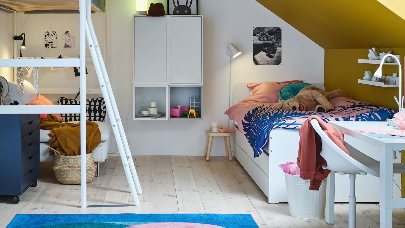 Ein Kinderzimmer für zwei Kinder mit Hochbett, einem SLÄKT Bettgestell mit Unterbett, Wandelementen, Schränken, Regalen und einem bunten Teppich.