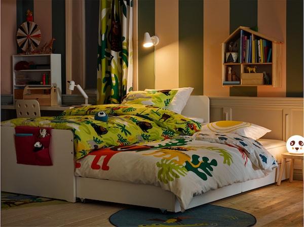 Ein Kinderzimmer im Abendmodus, u. a. mit dem SLÄKT Bettgestell mit Unterbett und Aufbewahrung