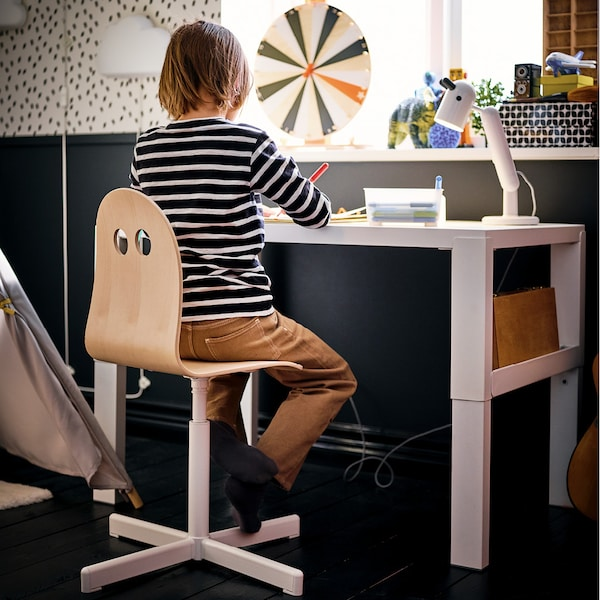 Ein Kinderzimmer mit 2 Schreibtischen und praktischen Utensilien