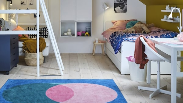 Ein Kinderzimmer mit einem Hochbett, einem weißen Bettrahmen, Wandelementen und Schränken, einem weißen Schreibtisch und einem rosa/grünen Teppich.