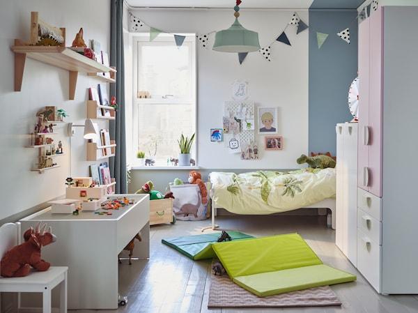 Ein Kinderzimmer mit einem Kleiderschrank in Weiß/Blassrosa, einer grünen Gymnastikmatte, einem weißen Spieltisch mit Stauraum und Stofftierdinosauriern