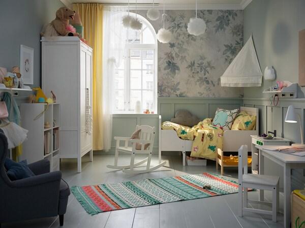 Ein Kinderzimmer mit einem SUNVIK Bettgestell, einem weißen Betthimmel, bunten Teppichen, weißem Kleiderschrank, Schaukelstuhl, weißem Tisch und Stuhl.