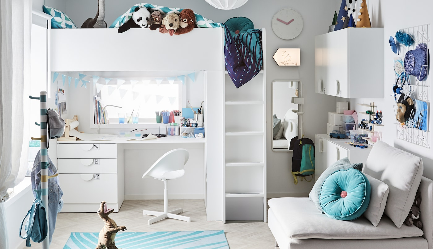 Ein Kinderzimmer mit einem weißen SMÅSTAD Hochbett mit einem Schreibtisch darunter steht an einer Wand. In der Nähe befindet sich ein weißes SÖDERHAMN Sitzelement.