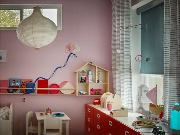 Ein Kinderzimmer mit gestreiften Gardinen und einem TRETUR Verdunklungsrollo, das zur Hälfte heruntergelassen ist.