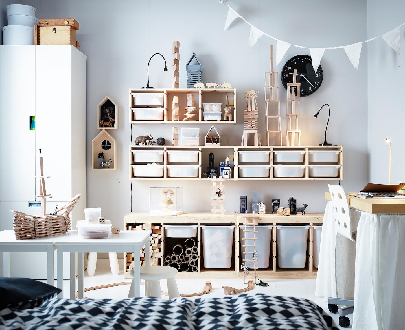 Ein Kinderzimmer mit Möbeln aus Kiefernholz und vielen Bauklötzen.