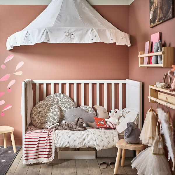 Ein Kinderzimmer mit Wänden in Rosa und einem weißen Babybett mit vielen kuscheligen Textilien und Stofftieren, einem weißen Betthimmel darüber und zwei Kinderhockern in Kiefer davor
