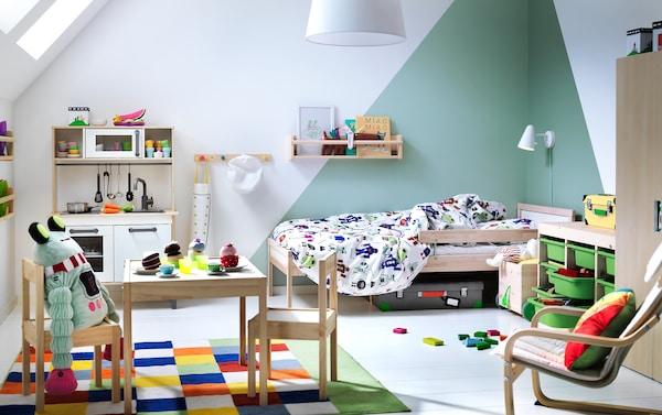 Ein Kinderzimmer u. a. mit SNIGLAR Juniorbettgestell mit Lattenrost in Buche, DUKTIG Spielküche, DUKTIG Kaffee-/Teeservice und LÄTT Kindertisch mit zwei Stühlen