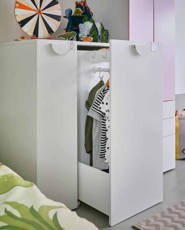 Ein Kleiderschrank mit Auszug in Weiß/Blassrosa, bei dem der Auszug offen steht. Darin befinden sich eine Kleiderstange und Haken. Daran hängt Kleidung an Kleiderbügeln.