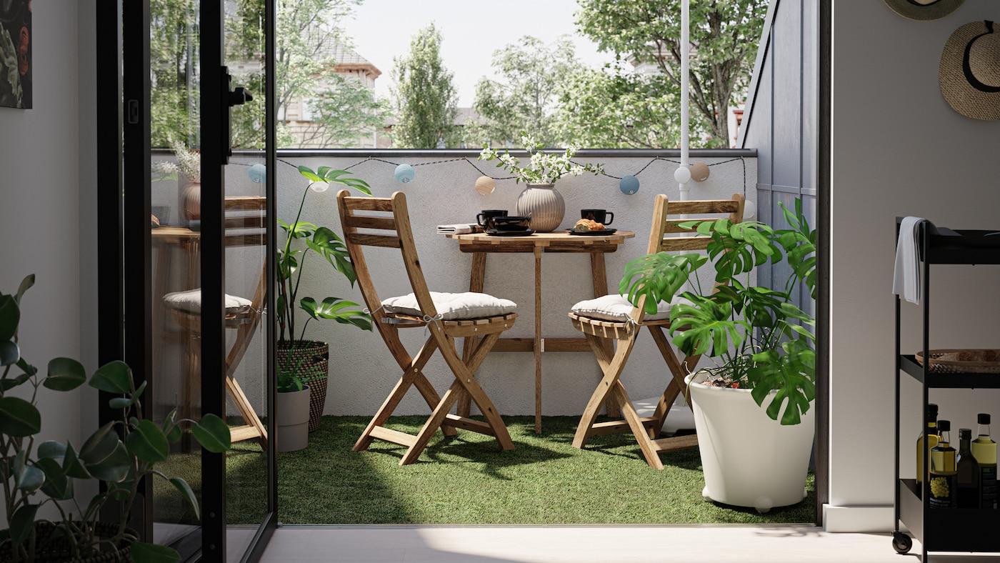 Ein kleiner Balkon mit Holztisch und –stühlen, Bodenrost mit Kunstgras und einer Monstera in einem weißen Übertopf.