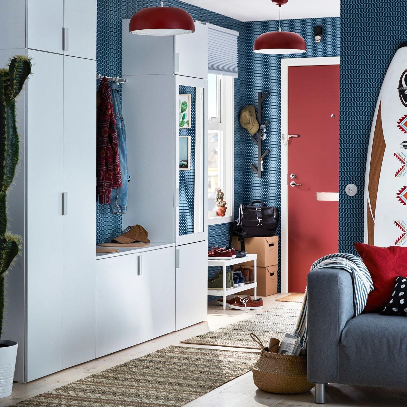 Ein kleiner Flur in Blau, Rot und Weiss mit einem weissen PLATSA Kleiderschrank mit FONNES Fronten in Weiss und RIDABU Spiegeltür.