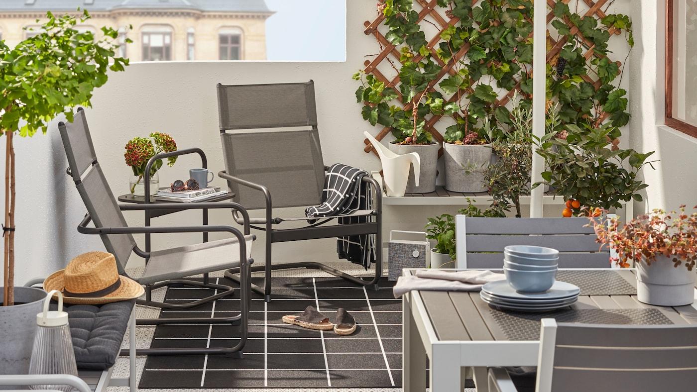 Ein kleiner, schön gestalteter Balkon mit HUSARÖ Sesseln und einem Beistelltisch hinter einem Esstisch mit Stühlen in Grau.
