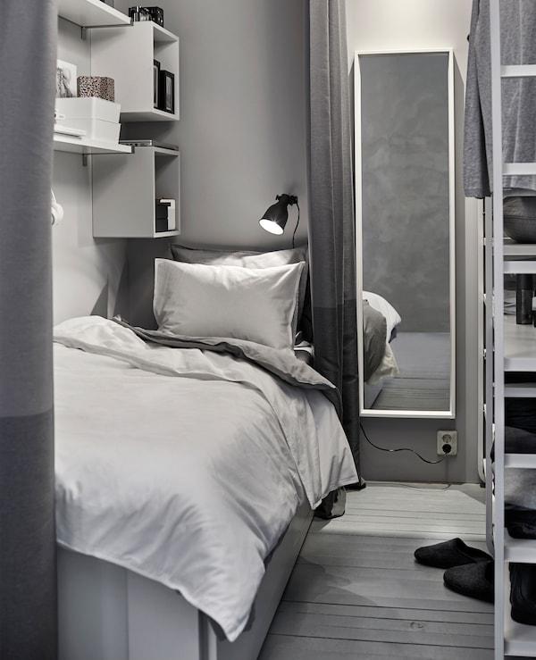 Ein kleiner, weiß und grau eingerichteter Schlafbereich in einem Gemeinschaftsbereich mit Kleiderschrank, u. a. mit BRIMNES Tagesbettgestell mit 2 Schubladen in Weiß