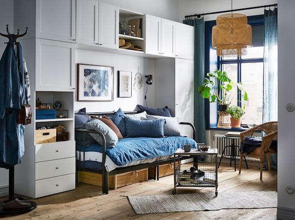 Ein kleines Apartment in Blau und Weiß mit PLATSA Kleiderschrank mit FONNES und SANNIDAL Fronten in Weiß, der um einen Schlaf-/Wohnzimmerbereich herumarrangiert wurde