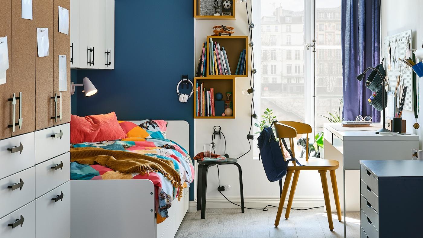 Ein kleines Jugendzimmer eingerichtet mit einem weissen Bett, einem Kleiderschrank  und an die Wand montierten Regalelementen in Goldbraun.