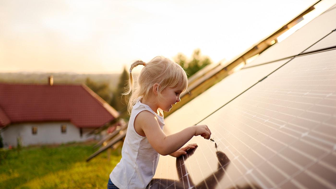 Ein kleines Kind berührt mit einem Grashalm eine Solarzelle auf dem Dach eines Hauses auf dem Land.