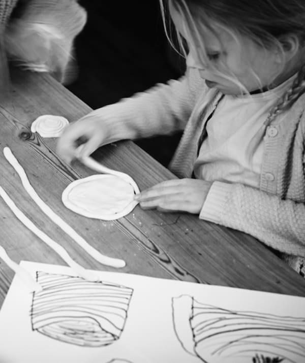 Ein kleines Mädchen steht an einem Tisch und ist ganz vertieft darin, Teigschnüre in eine scheibenförmige Konstruktion zu rollen, die später gebacken wird.