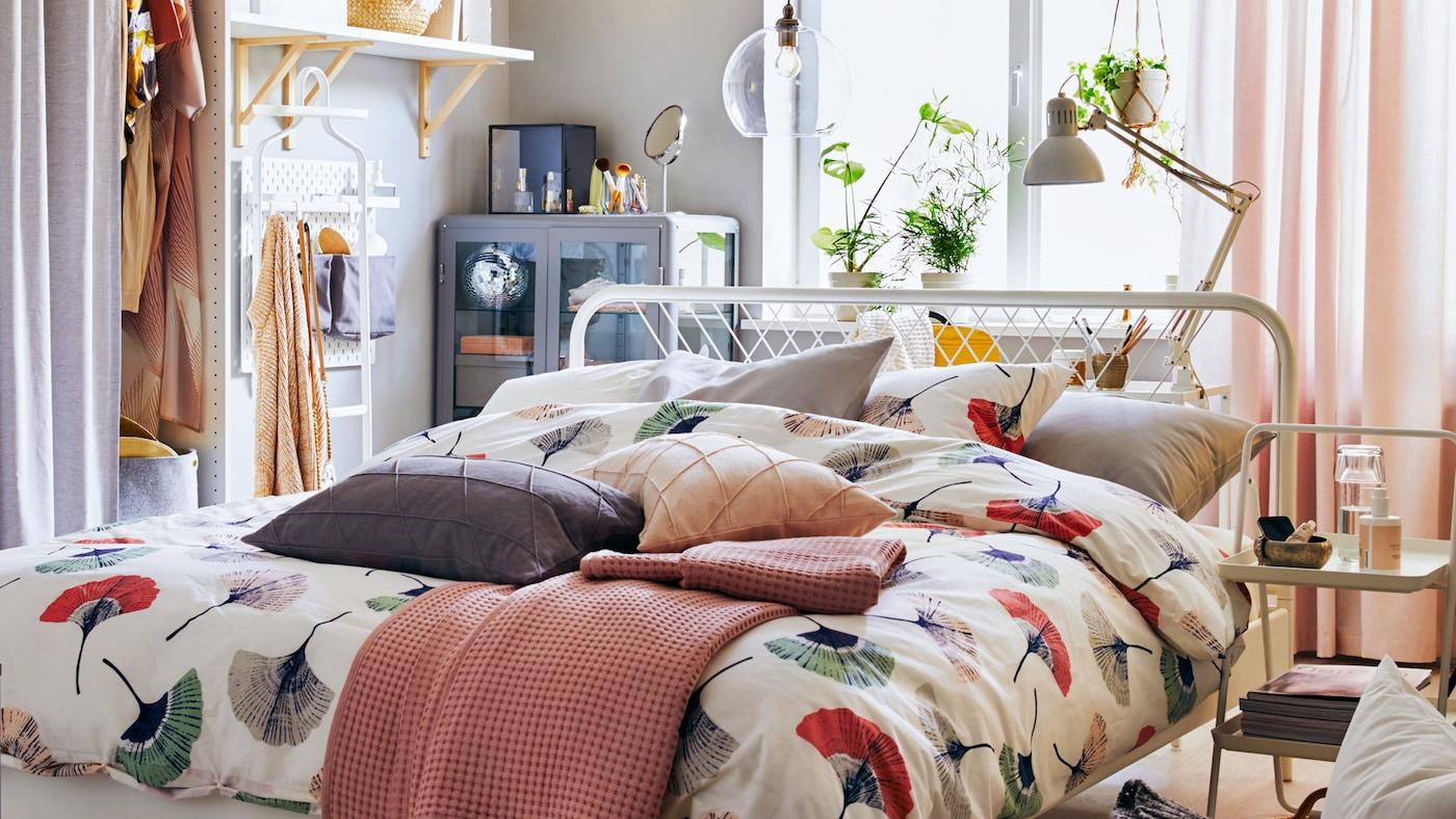 Ein kleines Schlafzimmer mit einem Bettgestell in der Mitte und Regalen an der Seite.