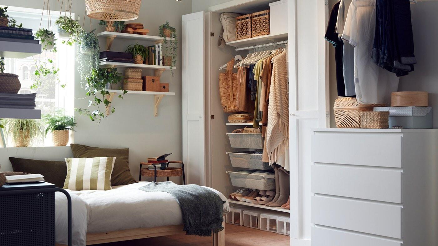 Ein kleines Schlafzimmer mit Holzbettgestell, einem Kleiderschranksystem mit gut organisierter Kleidung und Regalen mit Boxen und Pflanzen.
