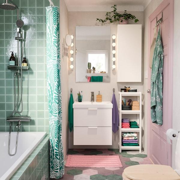 Ein kleines und buntes Badezimmer mit weißem Waschbecken, pinker Badematte, Badspiegel, einem GODMORGON Waschbeckenschrank und einem türkisfarbenen Duschvorhang.