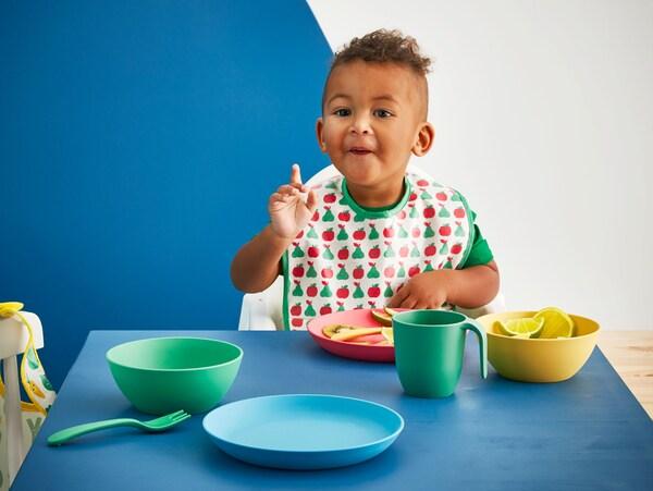 Ein Kleinkind isst an einem Tisch mit dem IKEA HEROISK Geschirr aus PLA-Kunststoff, u. a. HEROISK Schüssel in Gelb/Grün.