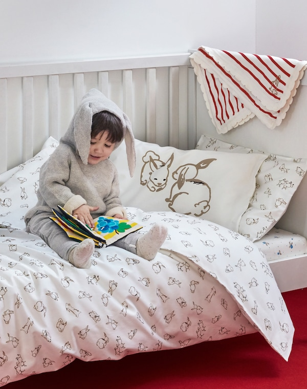 Ein Kleinkind sitzt in einem Strampelanzug mit Kapuze auf einem Bett und blättert in einem Kinderbuch. Über dem Kopfteil des Bettes hängend ist eine RÖDHAKE Babydecke zu sehen.