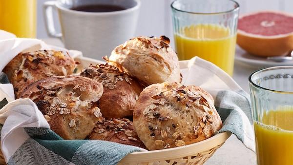 Ein KLYFTA Korb mit Hefeteilchen, die mit der HJÄLTEROLL Müsli hergestellt wurden, steht auf einem Frühstückstisch neben einer Tasse Kaffee, KALLNA Gläsern mit Orangensaft und einer Grapefruithälfte auf einem Teller.