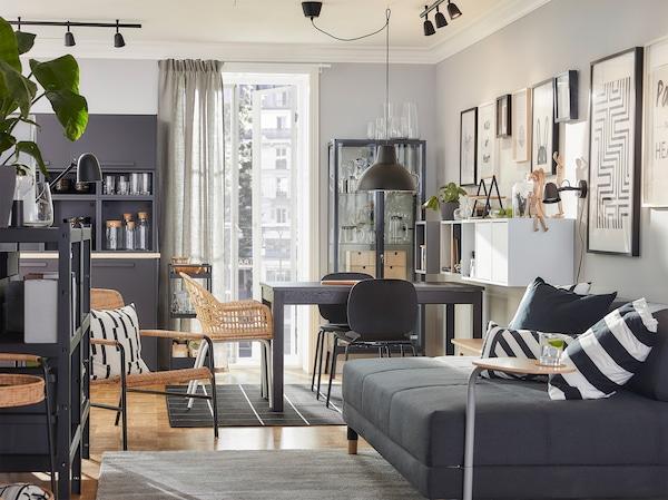Ein kombiniertes Wohn- und Esszimmer mit LANEBERG Ausziehtisch, Sessel aus Rattan, Schrankkombinationen, dunklem Bettsofa, Hängeleuchte und Teppichen.