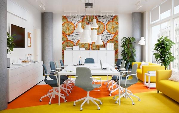 Ein Konferenzraum mit Akzenten in gelb & orange, weißen Tischen, grauen Drehstühlen & Pflanzen.