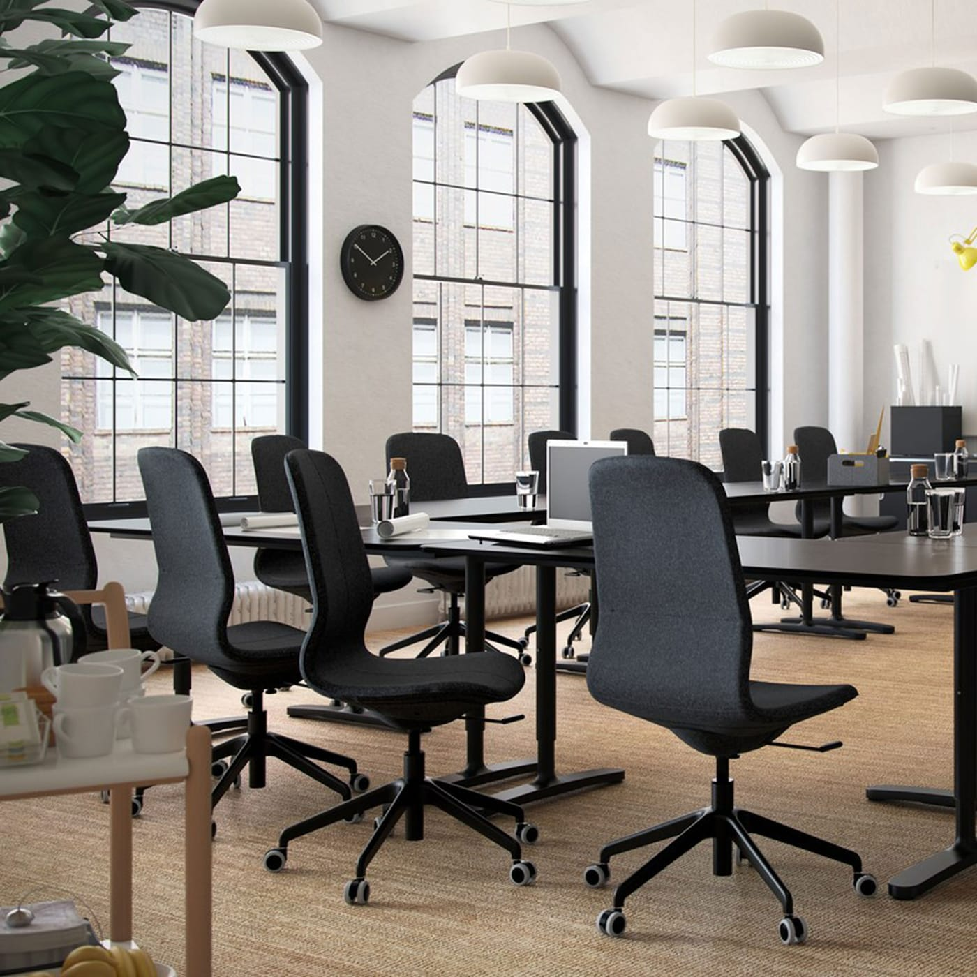 """Ein Konferenzraum mit BEKANT Schreibtischen in schwarzbraun/schwarz und LÅNGFJÄLL Drehstühlen mit Bezug """"Gunnared"""" dunkelgrau mit schwarzem Gestell."""