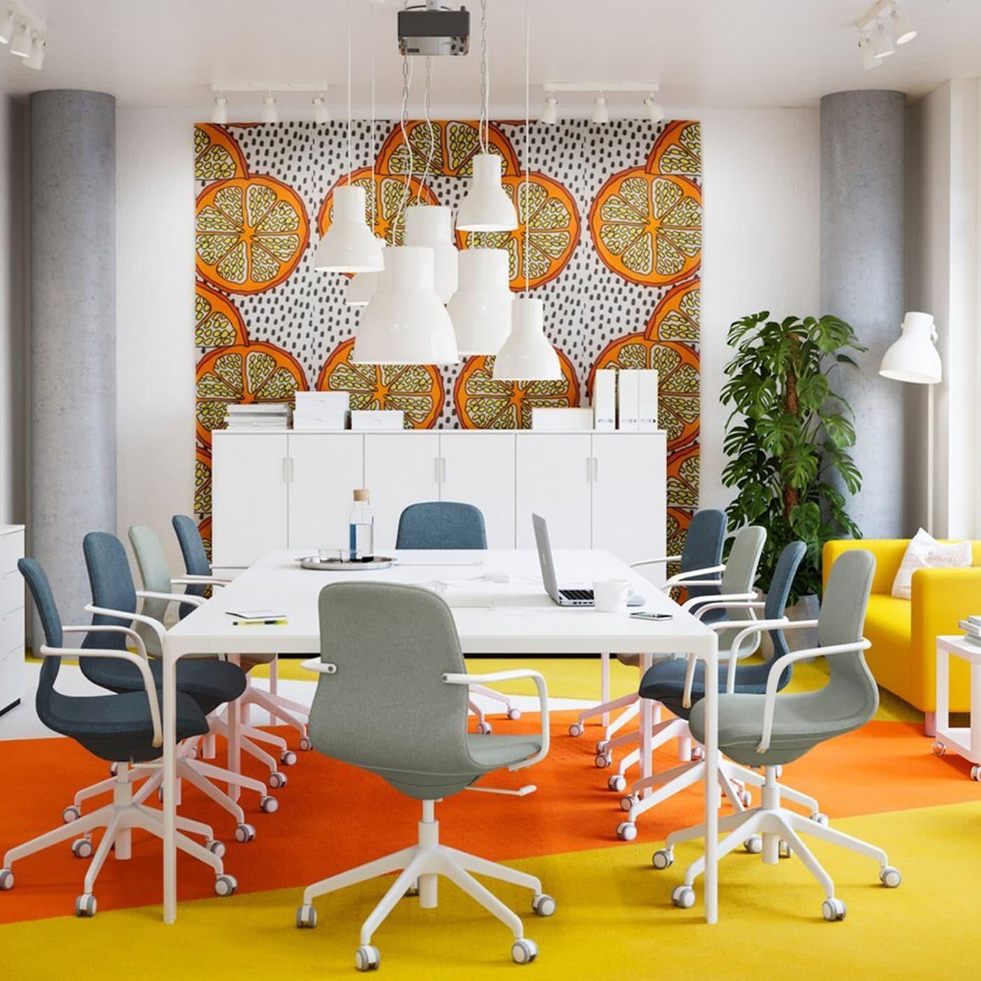 """Ein Konferenzzimmer in Gelb und Orange mit weißen Tischen und Drehstühlen, LÅNGFJÄLL Drehstühlen mit Bezug """"Gunnared"""" in hellgrün/weiß."""