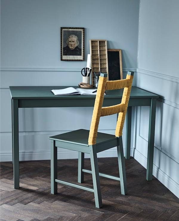 Ein kreativ gestalteter IVAR Stuhl aus Kiefer steht an einem olivgrünem Schreibtisch