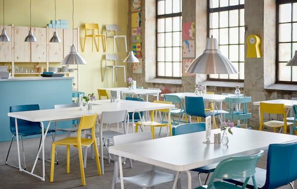 Ein kreatives & farbenfrohes Café mit weißen BACKARYD Tischen & Stühlen in Gelb, Türkis, Weiß & Blau