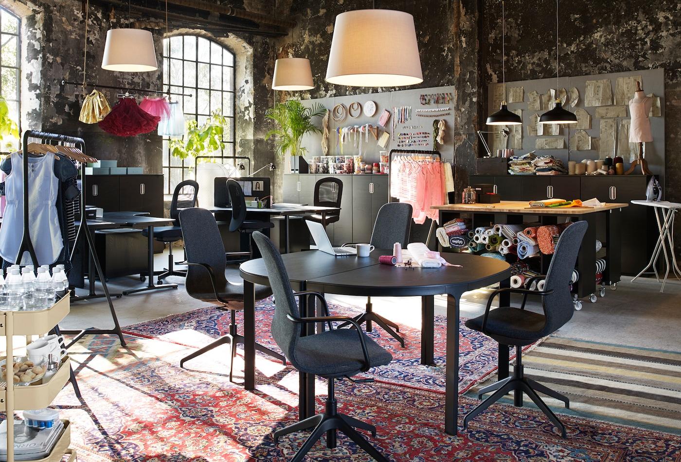 Ein kreatives Großraumbüro mit runden Konferenztischen, LÅNGFJÄLL Drehstühlen & bunten Teppichen