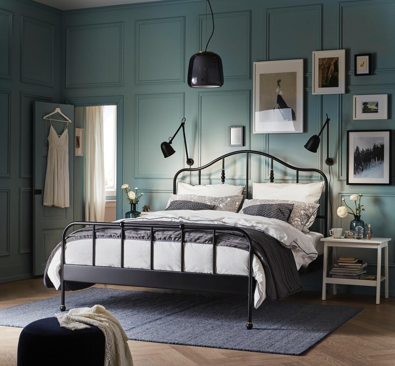 Ein kreatives, grünes Schlafzimmer mit schwarzem Doppelbett, weißem Bestelltisch und blauem Teppich.