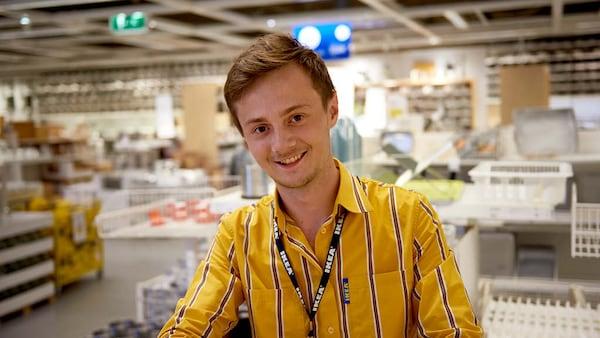 Ein lächelnder IKEA Lehrling zum Einzelhandelskaufmann steht im Einrichtungshaus