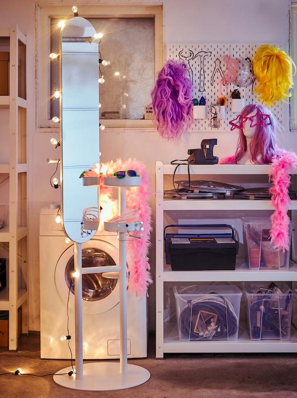 Ein LIERSKOGEN Kleiderständer sorgt hier mit einer BLÖTSNÖ Lichterkette dekoriert für Atmosphäre, während an einer SKÅDIS Lochplatte Perücken und Accessoires ihren Platz finden.