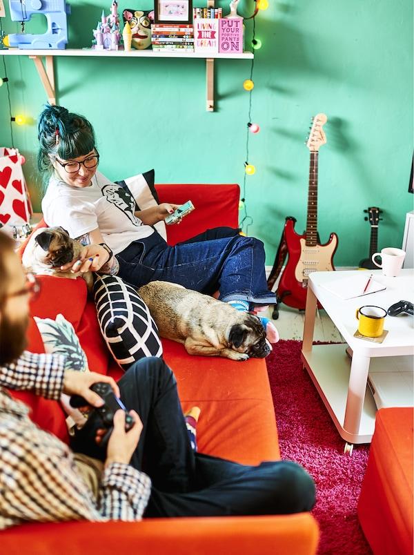 """Ein Loft mit BRÅTHULT Eckbettsofa mit Bezug """"Vissle"""" in Rot/Orange vor einer bunten Wand"""