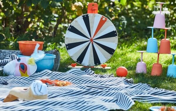 Ein LUSTIGT Glücksradspiel aus Holz neben anderen Spielen und bruchsicherem Geschirr auf einer Picknickdecke.