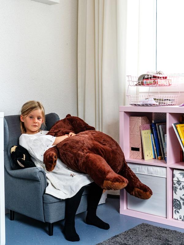 Ein Mädchen sitzt auf dem STRANDMON Sessel in Kindergrösse, das IKEA KALLAX bietet viel Stauraum in jedem Kinderzimmer.