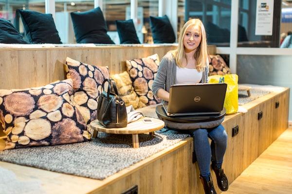 Ein Mädchen sitzt mit ihrem Laptop in einem IKEA Einrichtungshaus.