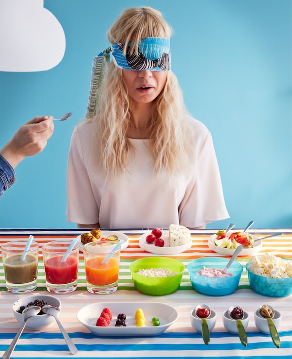 Ein Mädchen testet Essen mit verbundenen Augen, u. a. mit KALAS Schüsseln in verschiedenen Farben